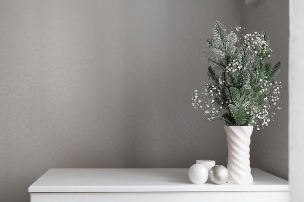 Neujahrsdekor minimalistische zusammensetzung von tannenzweigen und gypsophila in vase