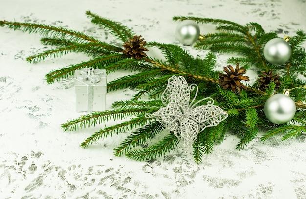 Neujahrsdekoration des hauses mit einem grünen fichtenzweig mit zapfen mit glänzenden kugeln und durchbrochenem silbernem schmetterling. weißer schneehintergrund.
