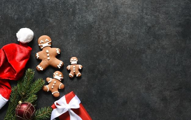 Neujahrsdekoration mit weihnachtsmütze, mandarinen und lebkuchen