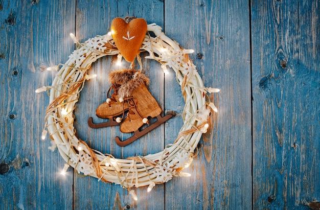 Neujahrsdekorationen um weihnachtsbrief leeren raum für text brennende lichter girlanden auf blauem holzhintergrund. sicht von oben. flach liegen. kopierraum brauner rustikaler stil