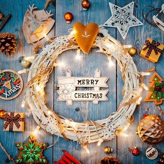 Neujahrsdekorationen um weihnachtsbrief leeren raum für text brennende lichter girlanden auf blauem holzhintergrund. sicht von oben. flach liegen.