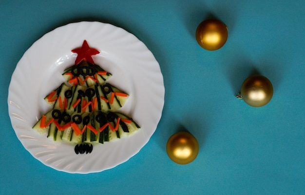 Neujahrsessen weihnachtsbaum aus gurkensalat auf blauem hintergrund mit weihnachtskugeln