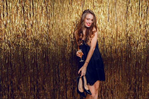 Neujahrsfeier. eine weiße glückliche verführerische frau, die mit glas champagner über goldenem funkeln aufwirft