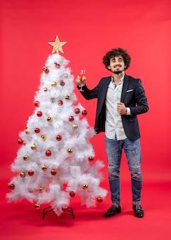 Neujahrsfeier mit bärtigem glücklichem jungem mann, der ein glas wein hält und steht