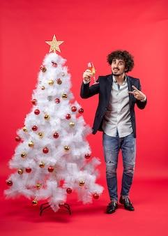 Neujahrsfeier mit einem glücklichen jungen mann, der ein glas wein hält, das siegesgeste macht