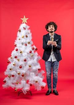 Neujahrsfeier mit jungem mann, der ein glas wein gibt und nahe geschmücktem weißem weihnachtsbaum steht