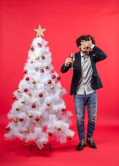 Neujahrsfeier mit jungem mann, der ein glas wein hält, das sein auge schließt