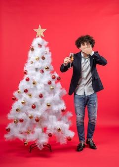 Neujahrsfeier mit jungem mann, der ein glas wein hält, das seinen mund schließt