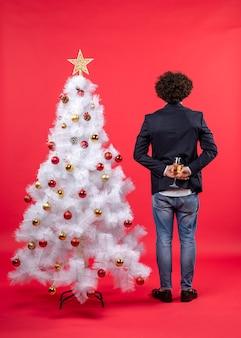 Neujahrsfeier mit jungem mann, der ein glas wein hinter geschmücktem weißem weihnachtsbaum hält
