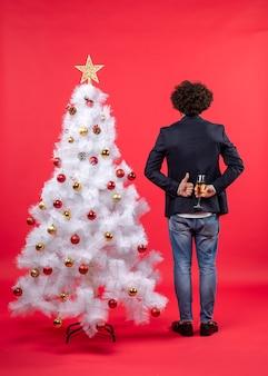 Neujahrsfeier mit jungem mann, der ein glas wein hinter sich hält und eine gute geste macht