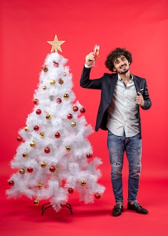 Neujahrsfeier mit jungem mann, der ein glas wein nahe verziertem weißem weihnachtsbaum auf rot erhebt