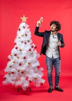 Neujahrsfeier mit jungem mann, der ein glas wein nahe verziertem weißem weihnachtsbaum auf rotem foto auf lager erhebt