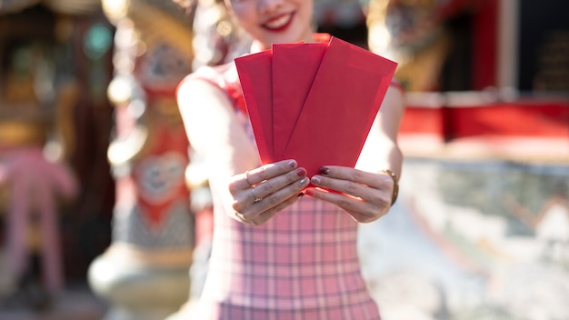 Neujahrsfeier mit roten umschlägen in den händen.