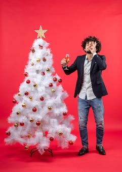 Neujahrsfeier mit schockiertem jungen mann, der ein glas wein hält, das perfekte geste macht