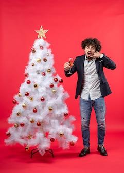 Neujahrsfeier mit schockiertem jungen mann, der ein glas wein hält, nennt mich geste