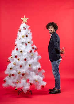 Neujahrsfeier mit überraschtem jungen mann, der ein glas wein hinter geschmücktem weißem weihnachtsbaum auf rot hält