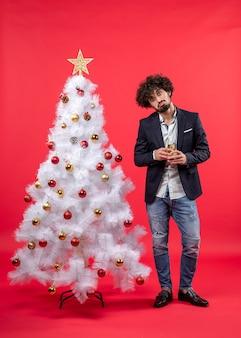 Neujahrsfeier mit verwirrtem jungen mann, der ein glas wein nahe verziertem weißem weihnachtsbaum hält