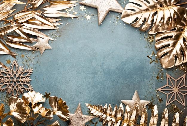 Neujahrsfeier und weihnachtshintergrund mit goldenen blumen, schnee, sternen und weihnachtsdekoration draufsicht.