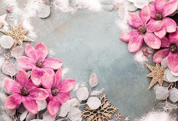 Neujahrsfeier und weihnachtshintergrund mit rosa blumen, schnee, sternen und weihnachtsdekorationen draufsicht.