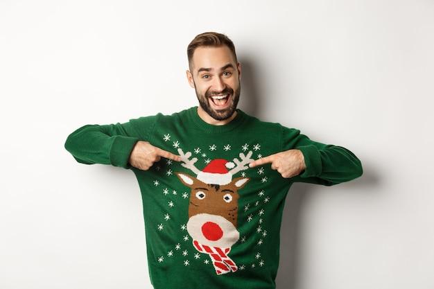 Neujahrsfeier und winterferienkonzept. fröhlicher mann, der auf seinen lustigen weihnachtspullover zeigt und lächelt, weißer hintergrund