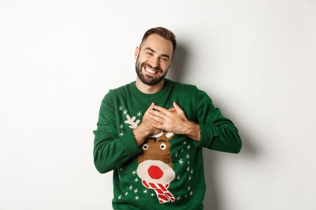 Neujahrsfeier und winterferienkonzept. glücklicher junger mann, der dankbar aussieht, die hände am herzen hält und sich für das weihnachtsgeschenk bedankt, der in einem lustigen pullover steht