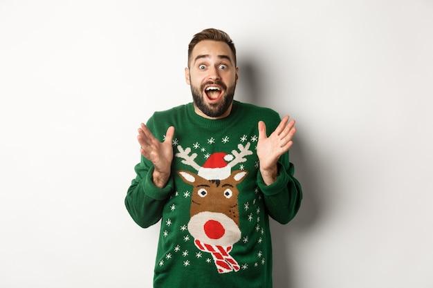 Neujahrsfeier und winterferienkonzept. glücklicher und überraschter bärtiger kerl, der erstaunt aussieht, etwas fängt, in lustigem weihnachtspullover steht, weißer hintergrund.