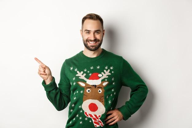 Neujahrsfeier und winterferienkonzept. selbstbewusster und glücklicher mann mit bart, der weihnachtspullover trägt und auf das banner in der oberen linken ecke zeigt, weißer hintergrund.