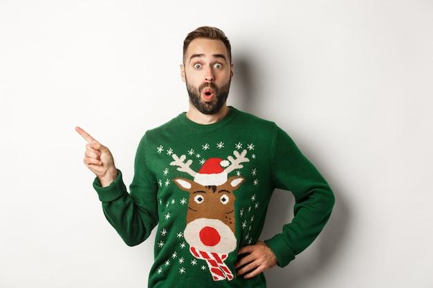 Neujahrsfeier und winterferienkonzept. überraschter mann im weihnachtspullover, der mit dem finger auf die obere linke ecke zeigt und erstaunt aussieht, weißer hintergrund