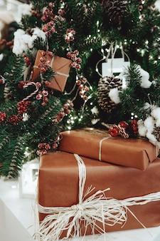 Neujahrsgeschenke unter dem weihnachtsbaum mit roten beeren und dekorationen