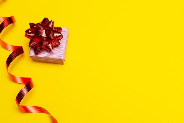 Neujahrsgeschenkplatz für geschenkliste geschenkbox mit roter schleife auf gelbem hintergrund