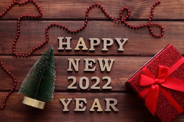 Neujahrsgrußkarte inschrift frohes neues jahr mit kleinem weihnachtsbaum und geschenkbox