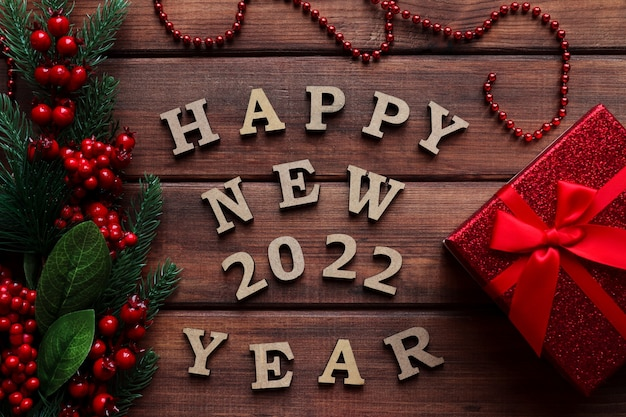 Neujahrsgrußkarte mit der aufschrift frohes neues jahr mit fichtenzweigbeeren-geschenkbox