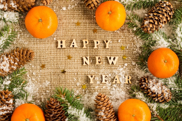 Neujahrshintergrund mit mandarinen auf sackleinen, fichtenzweigen und zapfen. rustikaler russischer stil.