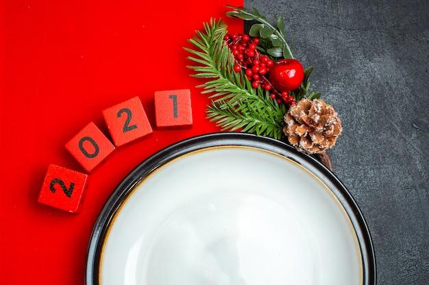 Neujahrshintergrund mit tafeltellerdekorationszubehör tannenzweigen und zahlen auf einer roten serviette auf einem schwarzen tisch