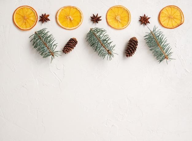 Neujahrskarte mit weihnachtsbaum und trockenen orangen, zapfen und anis, feiertagsschablone mit tanne und dekorationen