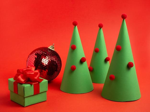 Neujahrskarte weihnachtsbaum aus papierkugel geschenkbox auf rotem hintergrund weihnachtshintergrund