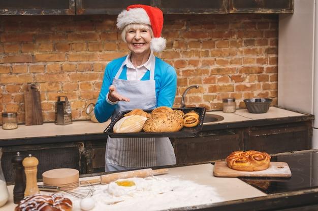 Neujahrskochen. porträt der attraktiven älteren älteren frau kocht auf küche. großmutter macht leckeres weihnachtsbacken.