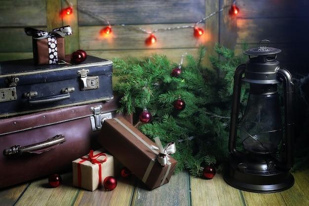 Neujahrskomposition aus zweigen von weihnachtsbäumen, die mit kugeln verziert sind vintage-lampe mit brennenden kerzen und kisten mit geschenken