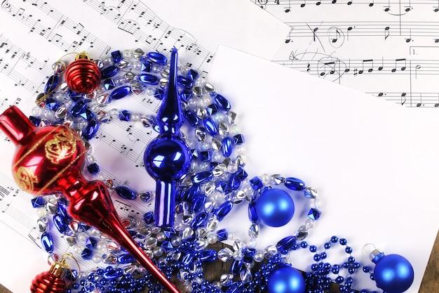 Neujahrskomposition weihnachtsbaumschmuck auf dem tisch und blatt mit musiknoten