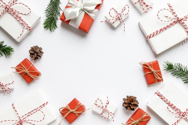 Neujahrskomposition. weihnachtsoberfläche mit rot und weiß verpackten geschenkboxen mit band, tannenzweigen, zapfen auf weißer oberfläche, kopierraum. winterferienmuster. draufsicht, flach liegen.