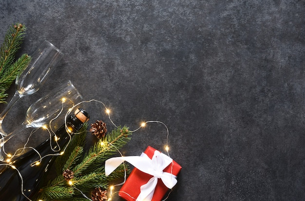 Neujahrskonzept. champagner und geschenkbox mit tanne auf dem neujahrstisch ..