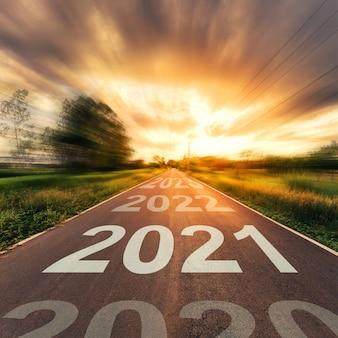 Neujahrskonzept: leerer asphaltstraßensonnenuntergang und neujahr 2021.