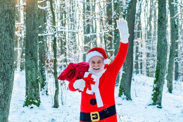 Neujahrskonzept. lieferung weihnachtsgeschenke. der weihnachtsmann kommt mit geschenken von außen. santa