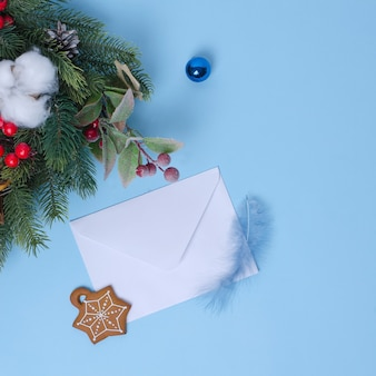 Neujahrskonzept mit einem weihnachtsbaum und weihnachtsdekorationen, ein weißer umschlag für einen brief auf einem blauen hintergrund liegt in der nähe.