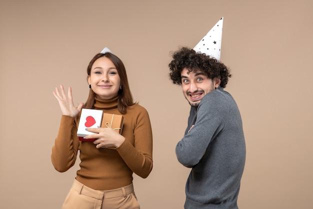 Neujahrskonzept mit jungem paar tragen neujahrshut glückliches mädchen mit herz und geschenk und lächelndem kerl auf grau