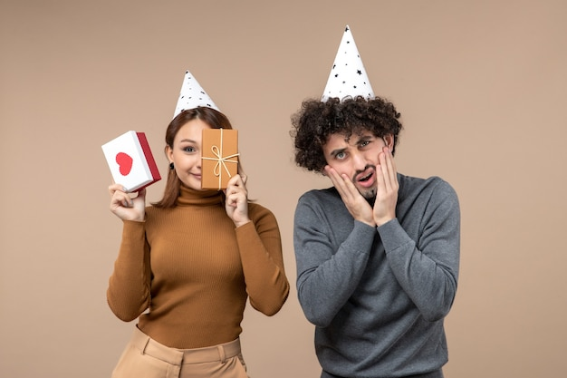 Neujahrskonzept mit jungem paar tragen neujahrshutmädchen, das ihr halbes gesicht herz und geschenk und schockierten kerl auf grau schließt