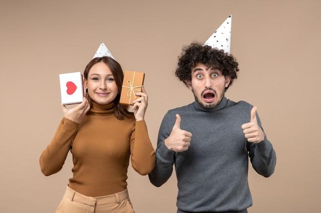 Neujahrskonzept mit schönem jungem paar tragen neujahrshut emotionales mädchen mit herz und geschenk