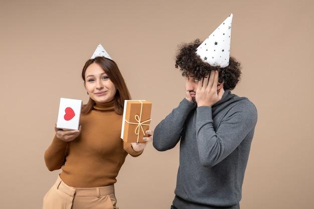 Neujahrskonzept mit schönen jungen paar tragen neujahrshut glückliches mädchen mit herz und geschenk