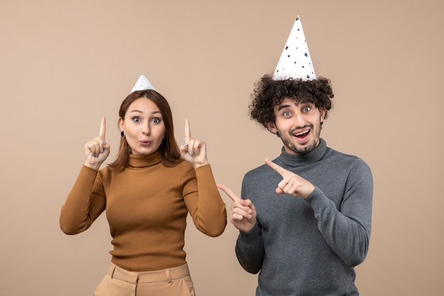 Neujahrskonzept mit verängstigtem jungem paar tragen neujahrshutmädchen und -mann auf grau