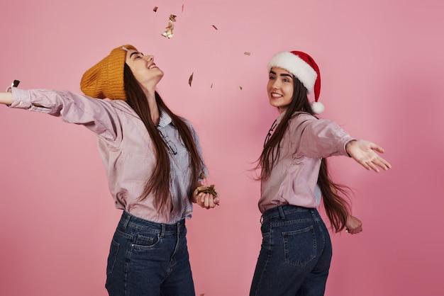 Neujahrskonzeption. zwei zwillinge spielen und werfen goldenes konfetti in die luft